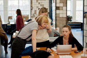 three women around a computer